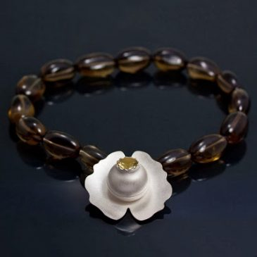Ett näckrossmycke med rökkvarts collier.  A water lily necklace with smoky quartz beads.