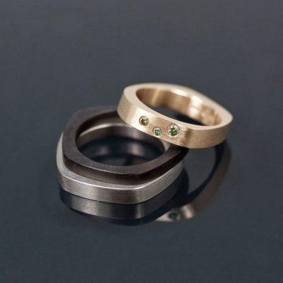 Hennes ring i rött guld med gröna diamanter satta med riven kant. Hans ringar i svartbrun akryl och titan.