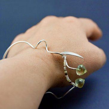 Ett lustfyllt armband av silver med gröna stenar. A bracelet of silver with green stones.