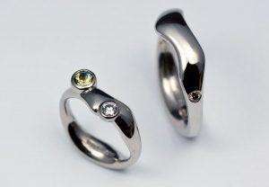 Vigselringar i vitguld med etiska diamanter och en grön safir.