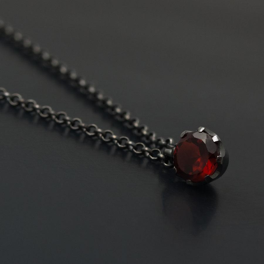 Halsband med granat i oxiderat silver.