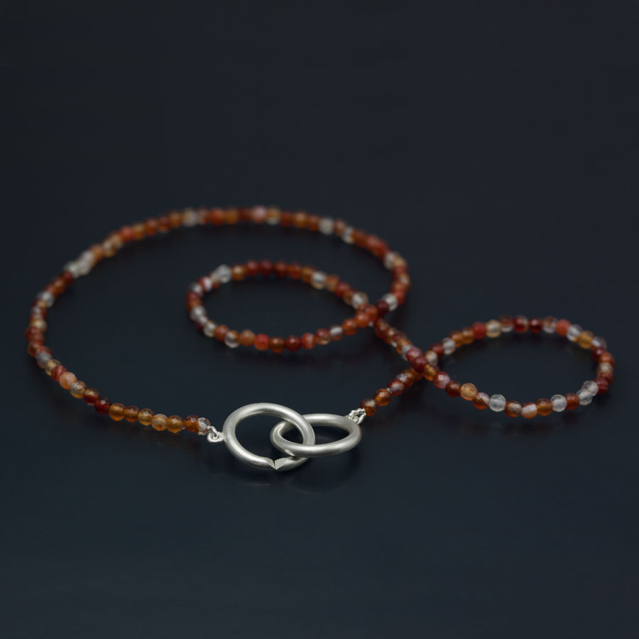 Karneoler med ett collierlås i form av två stora ringar. Enkelt och vackert.