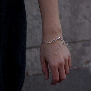 En armring av en oval silver tråd i from av ett klänge.