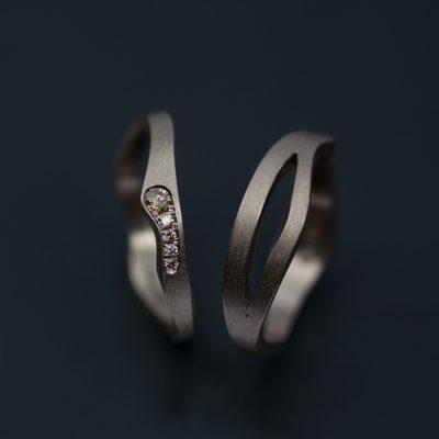 Vigselring och förlovningsring i vitt guld. Fattningen av kaffediamanterna är ett mellanting mellan faden och riven kant.