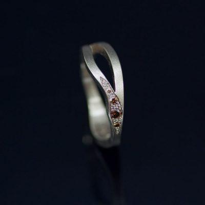 Vigselring i vitt guld. Kaffediamanterna är fattade med faden men spridda över en större yta med extra körn mellan stenarna.