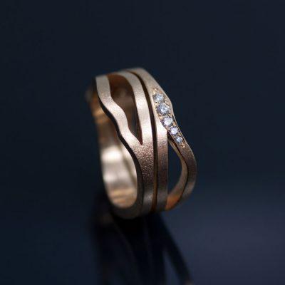 Vigsel och förlovningsring. Två pusslande rödguldsringar, fattade med en rad etiska diamanter satta med så kallad fadenfattning.