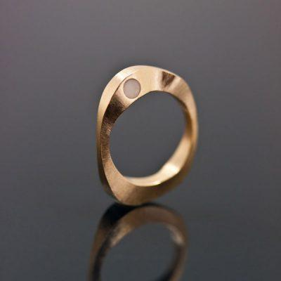 En organisk guldring med en specialslipad sten, en mjuk kvarts, som sitter skyddad på förlovningsringens sida.