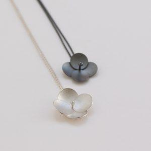 Enkelt och vackert. Silver blommor som berlocker på kedja. De via med saltvattenpärla, den oxiderade med hematitkula.