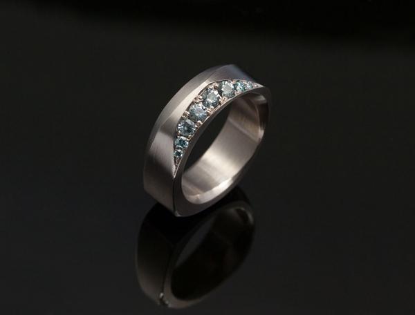 En geometrisk vigselring i vitguld med etiska ljusblå safirer och små färgade diamanter satta med fadenfattning. guldsmed; förlovningsring; safir; silversmed; smycken; vigselring; etisk; vitguld