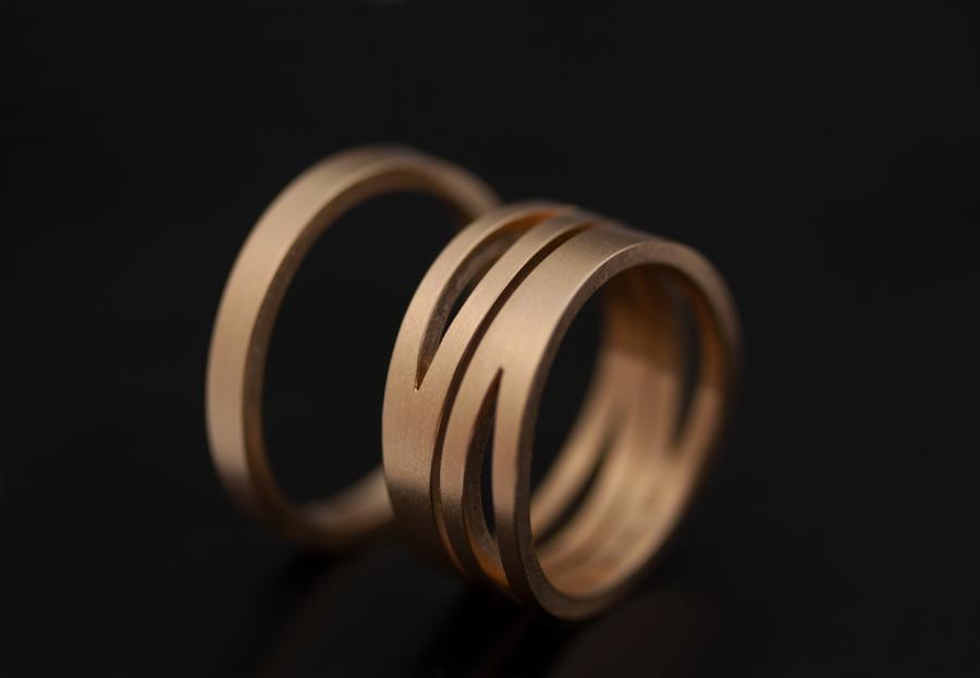 Pusslande symmetriska ringar i rött guld med matta ytor.