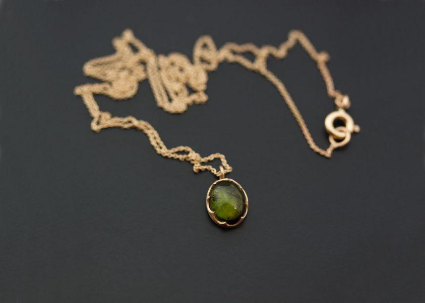 En grön turmalin satt i svenskt röd guld med en sargfattning.