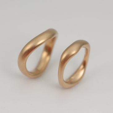 Mjuka förlovningsringar i rött guld.