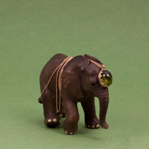 Elefant med berlock i guld och grön turmalin.