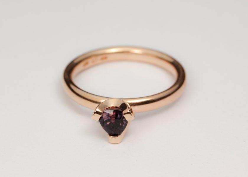 En förlovningsring i extra rött guld med oval ringskena och en mjuk fattning. Era rött guld och färgförändrande safir.