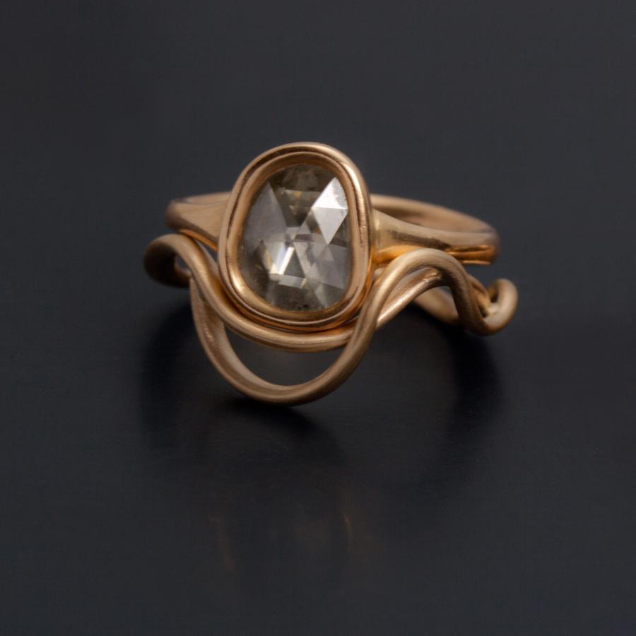En vigsel eller förlovningsring med stor rosenslipad diamant satt i en mjuk fattning av svenskt rödguld. Unde stenen har jag lagt en tunn platta av platina för att ge stenen dess rätta färg och lyster.