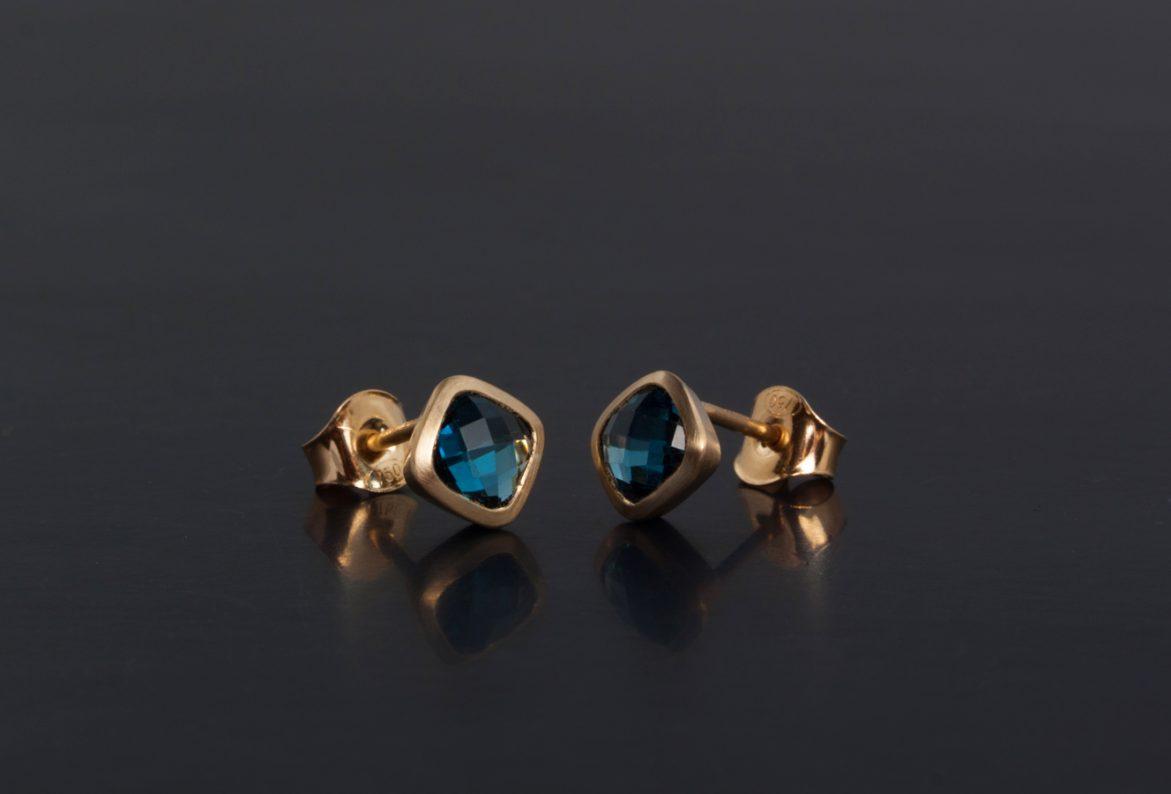 Örhängen i guld med mjukt fyrkantiga London blå topaser.