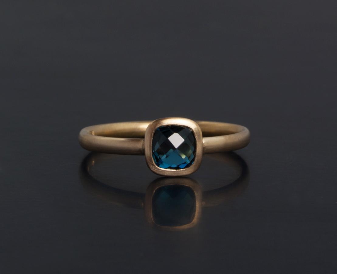 Låg och bekväm enstens ring i 18k guld med mjukt fyrkantig London blå topas