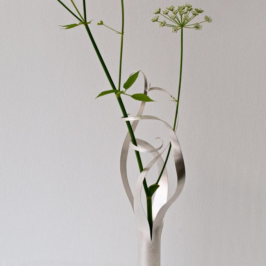 Lätta slingrande silver vaser och ljusstakar. Detalj av den stora vasen som håller så fint om sin blomma.