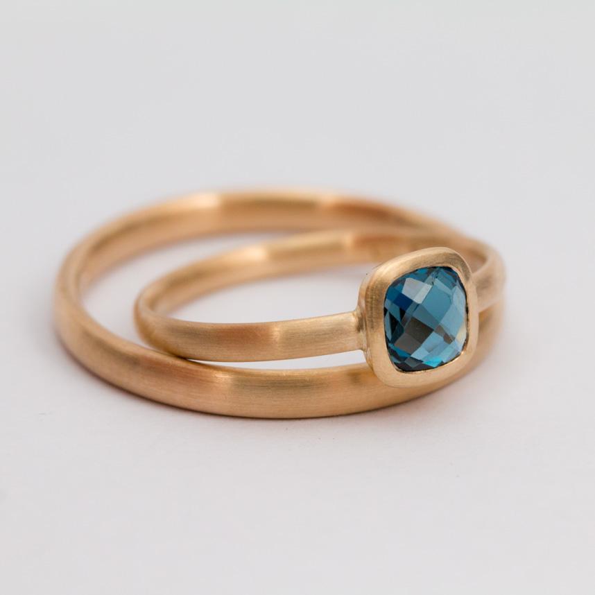 Vigsel eller förlovningsringar i rött 18k guld med rosenslipad Londonblå topas.