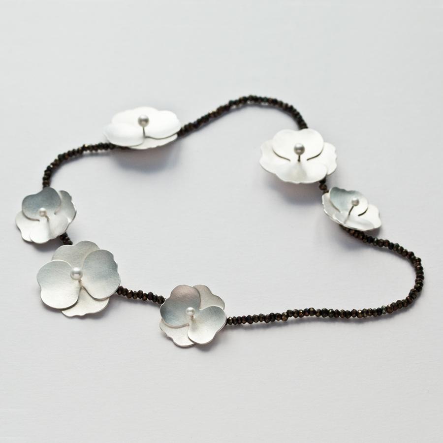 Sammetshortensia, blommande halssmycke i silver, halvborrade vita sötvattenspärlor och collier av bruna glittrande spineller.