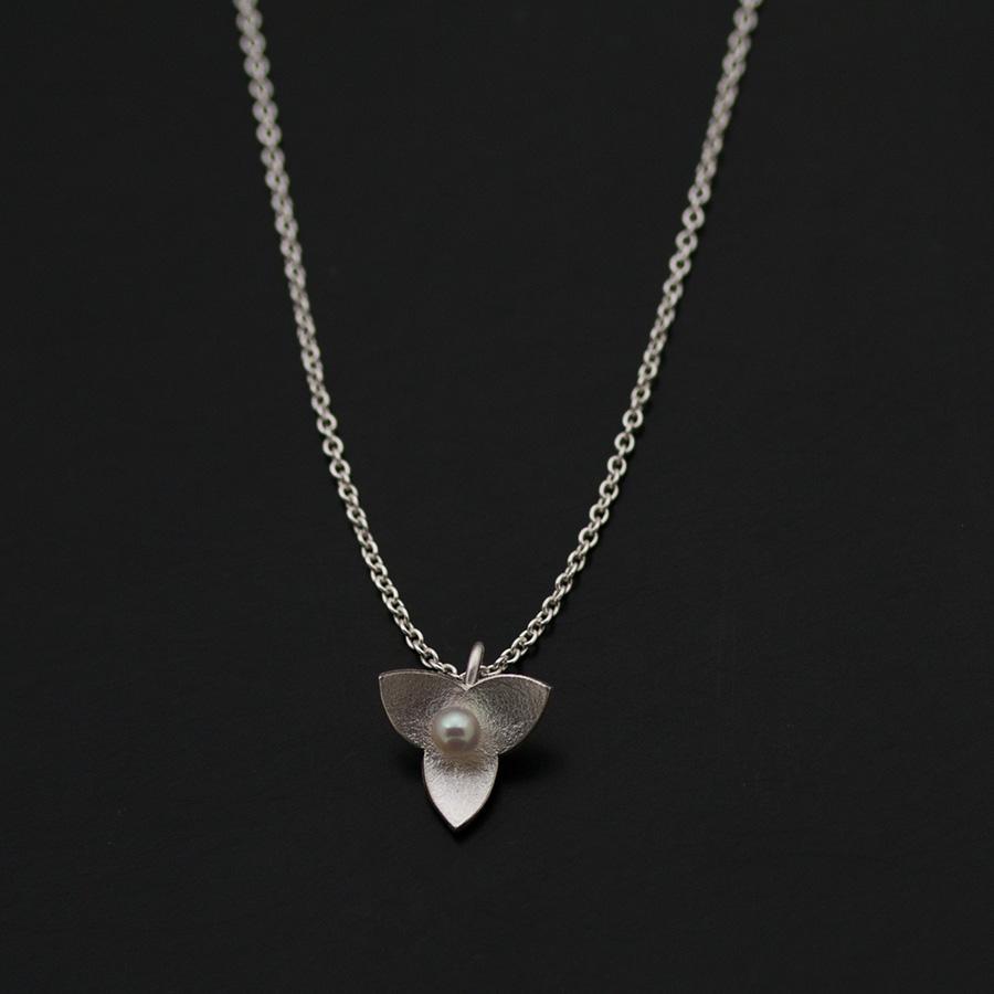 Små hängen i silver, oxiderat silver och silver med keumboo, silver täckt av en tunn plåt med 24k guld. Mitti berlockerna sitter vita sötvattenpärlor eller svarta kulor av hematit. Pärlor/kulor är 3 eller 2 mm i diamete. Formen kommer från blommorna på dvärgmåra.