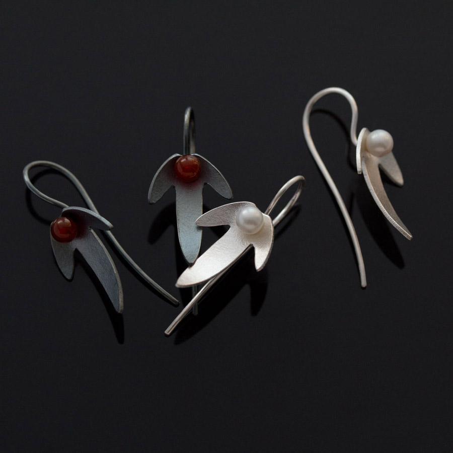 Örhängen av silver med vita sötvattenspärlor. Örhängen i oxiderat silver i mitten röd carneol. Formen hämtad från avenboksfrukter.