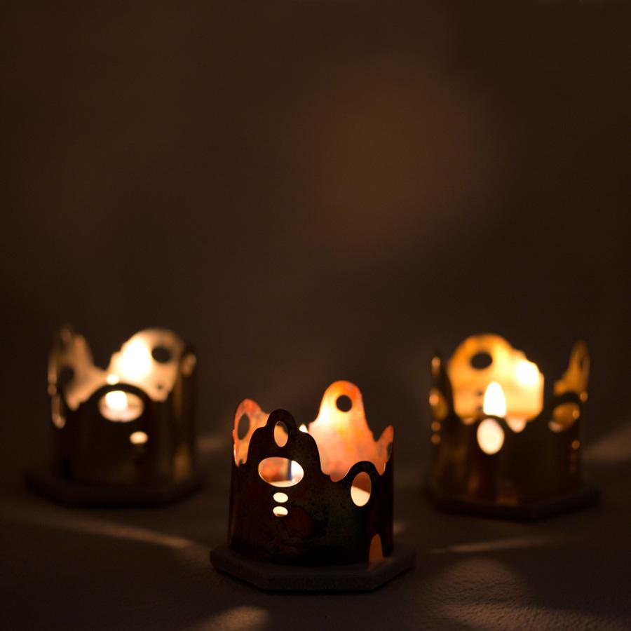 Ljuslycktor i form av hus eller ett runt kvarter i mässing brons och nysilver. Ritatde och tillverkade av Peronella Eriksson.